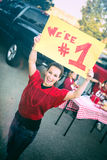Tailgating: Woman Holds Up Number One Sign For Team. Group of friends at a football tailgating party outside Stock Photos