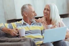 Taille d'un thé potable âgé joyeux de couples à la maison Photos stock