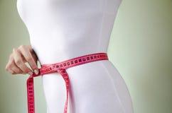 Taille d'une femme mince dans des sous-vêtements blancs avec la bande de mesure photographie stock libre de droits