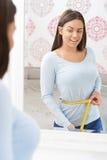 Taille de mesure d'adolescente heureuse dans le miroir Images libres de droits