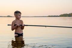 Taille de pêche de garçon profondément dans l'eau photos libres de droits