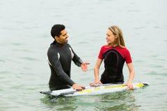 Taille de sourire de couples de surfers profondément dans l'eau image stock