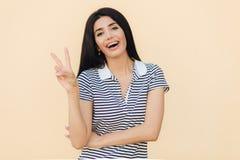 Taille herauf Porträt der jungen Frau des glücklichen Brunette zeigt Friedenszeichen, lächelt glücklich an der Kamera, trägt Klam stockfotografie