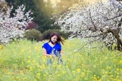 Taille herauf Porträt der jungen Frau in der hellen blauen Spitze auf blühendem Obstgarten und dem gelben Senfgebiet, Lächeln, ge stockbild