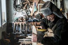 Taille herauf Porträt des alten Großvaters in der grauen warmen Kleidung in den Brillen, die hölzerne Planke sägen lizenzfreie stockbilder