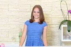 Taille oben der eleganten Frau 20s hinter Zähler Stockfotografie