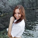 Taille op portret van glimlachende vrouwelijke persoon in wit overhemd stock afbeeldingen