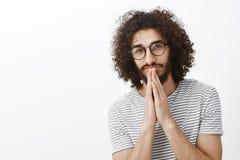 Taille-op schot van knap dromerig Spaans mannelijk model met baard en afrokapsel, dient het houden bidt dichtbij mond in en royalty-vrije stock foto's