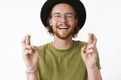 Taille-op schot van optimistische onbezorgde en knappe jonge gebaarde kerel in glazen en hoed lachen uit luid met blij royalty-vrije stock foto