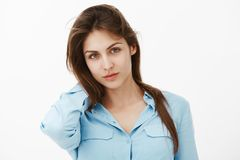 Taille-op schot van zekere flirty Europese vrouw die in blauwe blouse, terug van hals raken die, van onder voorhoofd kijken met royalty-vrije stock foto's