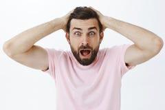Taille- tirée de l'homme choqué dans la bouche s'ouvrante de hurlement de panique peignant des cheveux avec des mains sur regarde image stock