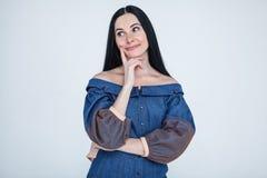 Taille- tirée espacée de la fille idiote de charme avec des cheveux de brune dans la robe élégante de jeans touchant le menton en photo stock