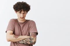 Taille- tirée jeune de l'homme aux cheveux bouclés fâché et pissé intense avec la moustache et des tatouages tenant l'offense à l photographie stock