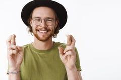 Taille- tirée jeune du voyageur masculin barbu heureux et aimable sincère faisant des espoirs ou le souhait avec les mains augmen images stock