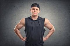 Taillen-obenporträt des hübschen jungen Mannes mit Muskeln mit seinen Händen auf Hüften stockfotografie
