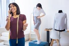 Tailleur émotif parlant au téléphone avec le client derrière elle de retour Images stock