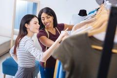 Tailleur émotif regardant le client tout en choisissant vêtx avec elle Photographie stock libre de droits
