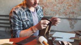 Tailleur assidu cousant un portefeuille pour des clients banque de vidéos