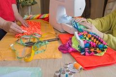 Tailleur de femme posant sur son lieu de travail avec le tissu coupé, l'espace libre sur le mur en bois la séance d'ouvrière cout Photographie stock libre de droits