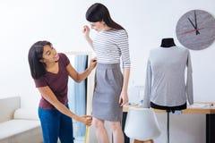 Tailleur heureux mesurant la longueur d'une robe et semblant heureux Image libre de droits