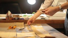 tailleur Tissu de ciseaux du ` s de tailleur de tailleur d'entaille de mains Matériel piquant de tailleur féminin sur le lieu de  Photos libres de droits