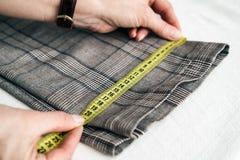 Tailleur utilisant une bande de mesure pour mesurer la largeur du pantalon image libre de droits