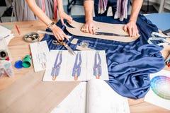 Tailleurs coupant le tissu bleu sur la table Photo libre de droits