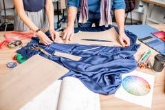 Tailleurs coupant le tissu bleu sur la table Photos stock