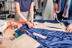 Tailleurs coupant le tissu bleu sur la table Photos libres de droits