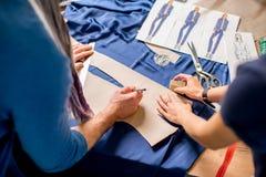 Tailleurs coupant le tissu bleu sur la table Photographie stock