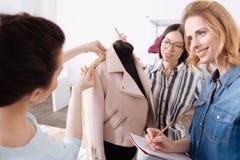 Tailleurs de jeunes travaillant avec une veste rose Photographie stock libre de droits