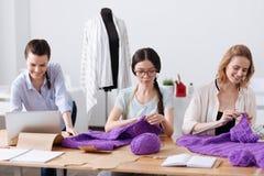 Tailleurs féminins d'atelier tricotant des écharpes Photographie stock libre de droits