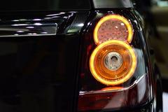 Taillight крупного плана черной предпосылки автомобиля Стоковые Изображения RF