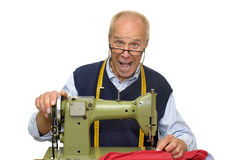 Tailor. Mature tailor with a sewing machine isolated in white royalty free stock photos