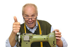 Tailor. Mature tailor with a sewing machine isolated in white royalty free stock photo