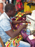 A tailor. An african tailor while sewing colored fabrics with a sewing machine Stock Images