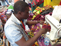 A tailor. An african tailor while sewing colored fabrics with a sewing machine Stock Photo