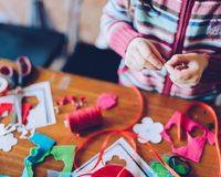 Tailor art workshops for children - a girl sewing felt decoratio. Ns - colorful fabrics lying on a table Stock Photography