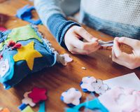 Tailor art workshops for children - a girl sewing felt decoratio. Ns - colorful fabrics lying on a table Royalty Free Stock Photography