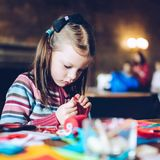 Tailor art workshops for children - a girl sewing felt decoratio. Ns - colorful fabrics lying on a table - a little girl slipping a needle Stock Images