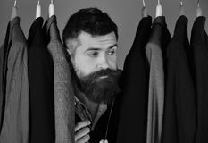 Tailor with bored face near custom jackets on blue background,. Close up. Fashion choice concept. Man with beard in vest by clothes rack. Designer hides among Stock Photography