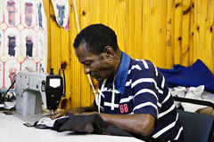 Tailor business. African man sewing in a small tailor shop, industrial sewing machine, African small industry royalty free stock photo
