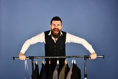 Tailor with cheerful face near custom jackets on blue background royalty free stock photos