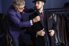 Tailor with client in atelier. Sewing custom made suit. Portrait of mature professional tailor fitting bespoke suit to male model in exclusive atelier studio royalty free stock photos
