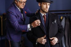 Tailor with client in atelier. Sewing custom made suit. Portrait of mature professional tailor fitting custom made coat to male model in exclusive atelier studio royalty free stock photos