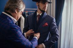 Tailor with client in atelier. Sewing custom made suit. Portrait of mature professional tailor fitting custom made coat to male model in exclusive atelier studio stock photography