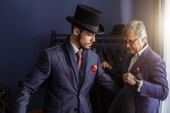 Tailor with client in atelier. Sewing custom made suit. Young, handsome and successful businessman trying on a bespoke stylish suit at tailors shop. Dressmaking stock photography
