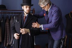 Tailor with client in atelier. Sewing custom made suit. Young, handsome and successful businessman trying on a custom made stylish suit at tailors shop royalty free stock image