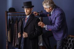 Tailor with client in atelier. Sewing custom made suit. Young, handsome and successful businessman trying on a custom made stylish suit at tailors shop stock photo