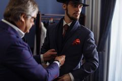 Tailor with client in atelier. Sewing custom made suit. Young, handsome and successful businessman trying on a custom made stylish suit at tailors shop royalty free stock images